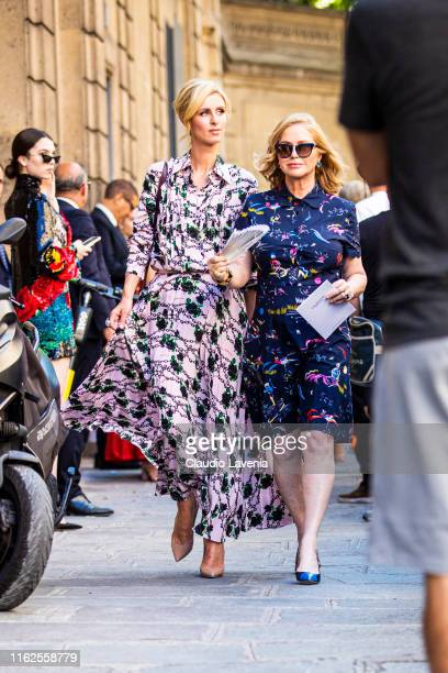 Nicky Hilton , wearing a pink printed long dress and nude heels, and Kathy Hilton , wearing a blue printed shirt with matching skirt and blue and...