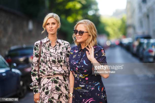 Nicky Hilton wears a pale pink dress with floral print Kathy Hilton wears a dark blue dress with multicolor printed features sunglasses outside...