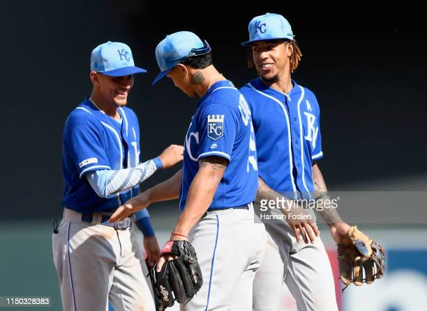 Nicky Lopez, Cheslor Cuthbert and Adalberto Mondesi of the Kansas City Royals celebrate defeating the Minnesota Twins after the game on June 16, 2019...