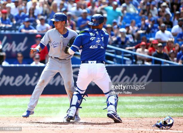 Nicky Lopez of the Kansas City Royals is caught stealing home by catcher Luke Maile of the Toronto Blue Jays in the ninth inning during a MLB game at...