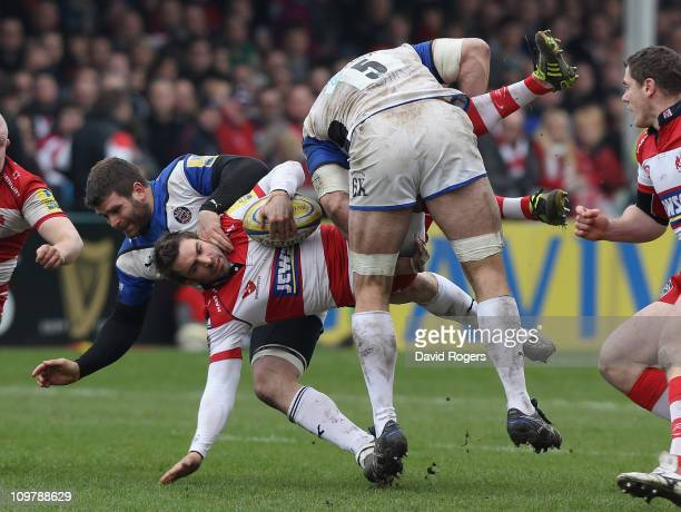 Nicky Robinson of Gloucester is up ended by Luke Watson and Danny Grewcock during the Aviva Premiership match between Gloucester and Bath at...