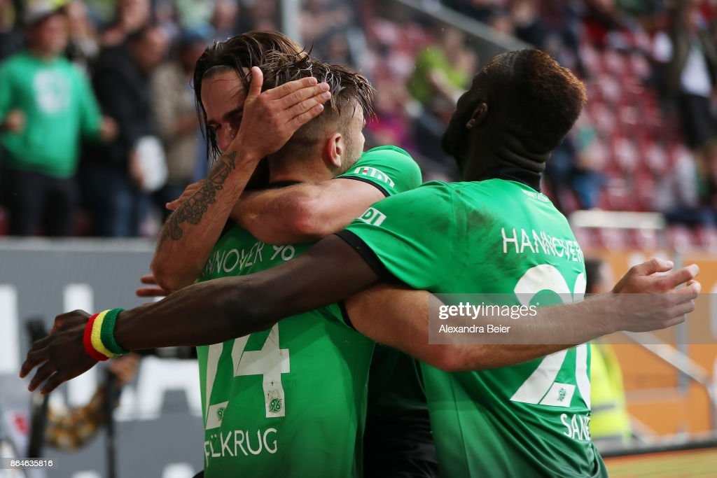 Niclas Fuellkrug of Hannover celebrates with Martin Harnik of Hannover (behind) and Salif Sane of Hannover (r) after he scored the winning goal for Hannover to make it 1:2 during the Bundesliga match between FC Augsburg and Hannover 96 at WWK-Arena on October 21, 2017 in Augsburg, Germany.