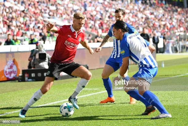 Niclas Fuellkrug of Hannover is challenged by Karim RekikÊ of Berlin during the Bundesliga match between Hannover 96 and Hertha BSC at HDIArena on...