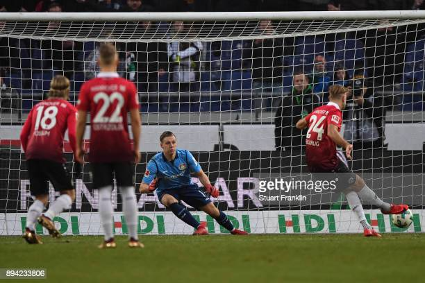 Niclas Fullkrug of Hannover 96 scores from the penalty against Bernd Leno of Bayer Leverkusen to make it 21 during the Bundesliga match between...