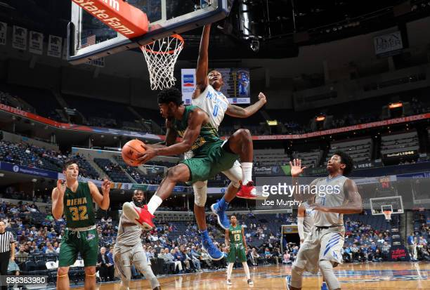 Nico Clareth of the Siena Saints looks to pass to Evan Fisher of the Siena Saints against Kyvon Davenport of the Memphis Tigers on December 20 2017...