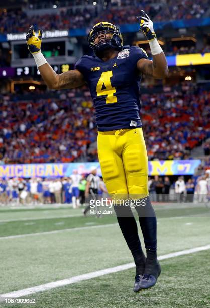 Nico Collins of the Michigan Wolverines celebrates a first quarter touchdown by teammate Donovan PeoplesJones against the Florida Gators during the...