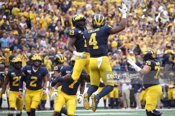 Nico Collins of the Michigan Wolverines celebrates his first quarter touchdown with Mike Sainristil while playing the Rutgers Scarlet Knights at...