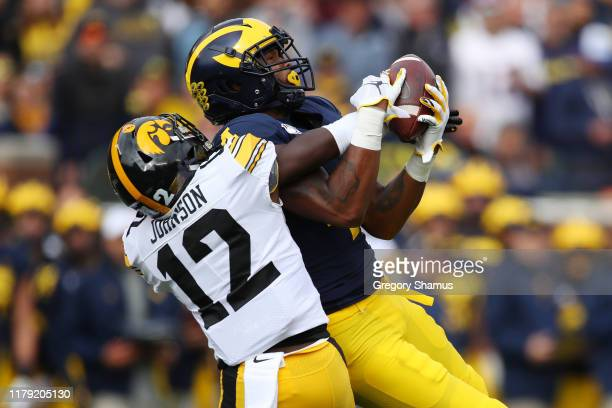 Nico Collins of the Michigan Wolverines makes a first quarter catch against DJ Johnson of the Iowa Hawkeyes at Michigan Stadium on October 05 2019 in...