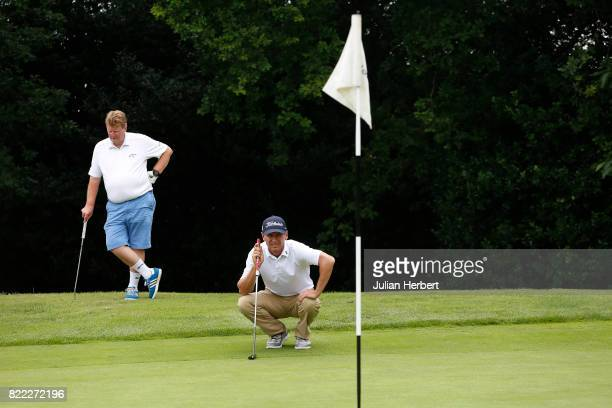 Nico Els of Professional Golf Tuiton Breaks is watched by Gary Greengrass as he lines up a putt during The Lombard Trophy PGA South Qualifier at...