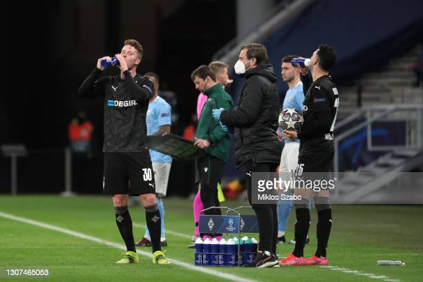 Nico Elvedi and Ramy Bensebaini of Borussia Moenchengladbach take a drink during the UEFA Champions League Round of 16 match between Manchester City...