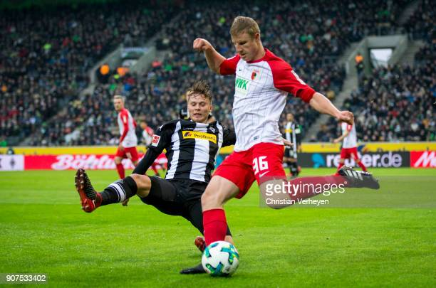 Nico Elvedi of Borussia Moenchengladbach and Martin Hinteregger of FC Augsburg battle for the ball during the Bundesliga match between Borussia...