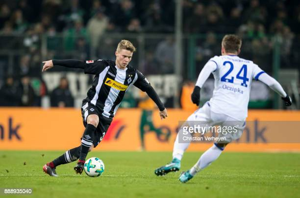 Nico Elvedi of Borussia Moenchengladbach is attacked by Bastian Ocipka of FC Schalke 04 during the Bundesliga match between Borussia Moenchengladbach...