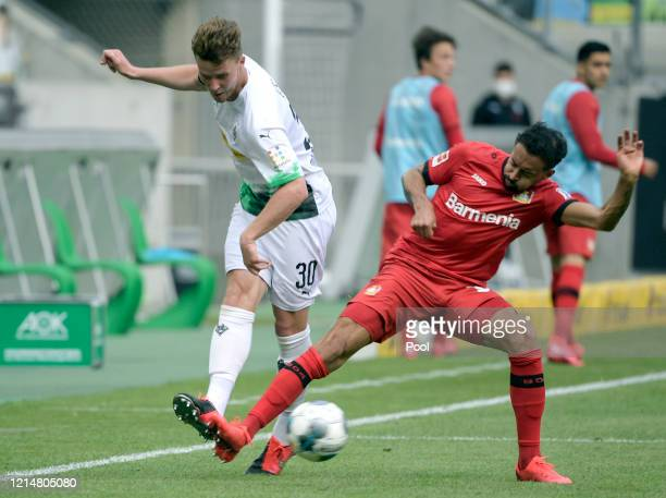 Nico Elvedi of Borussia Moenchengladbach is challenged by Karim Bellarabi of Bayer 04 Leverkusen during the Bundesliga match between Borussia...