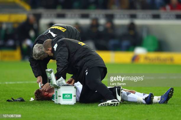 Nico Elvedi of Borussia Monchengladbach is given treatment following an injury during the Bundesliga match between Borussia Moenchengladbach and 1 FC...