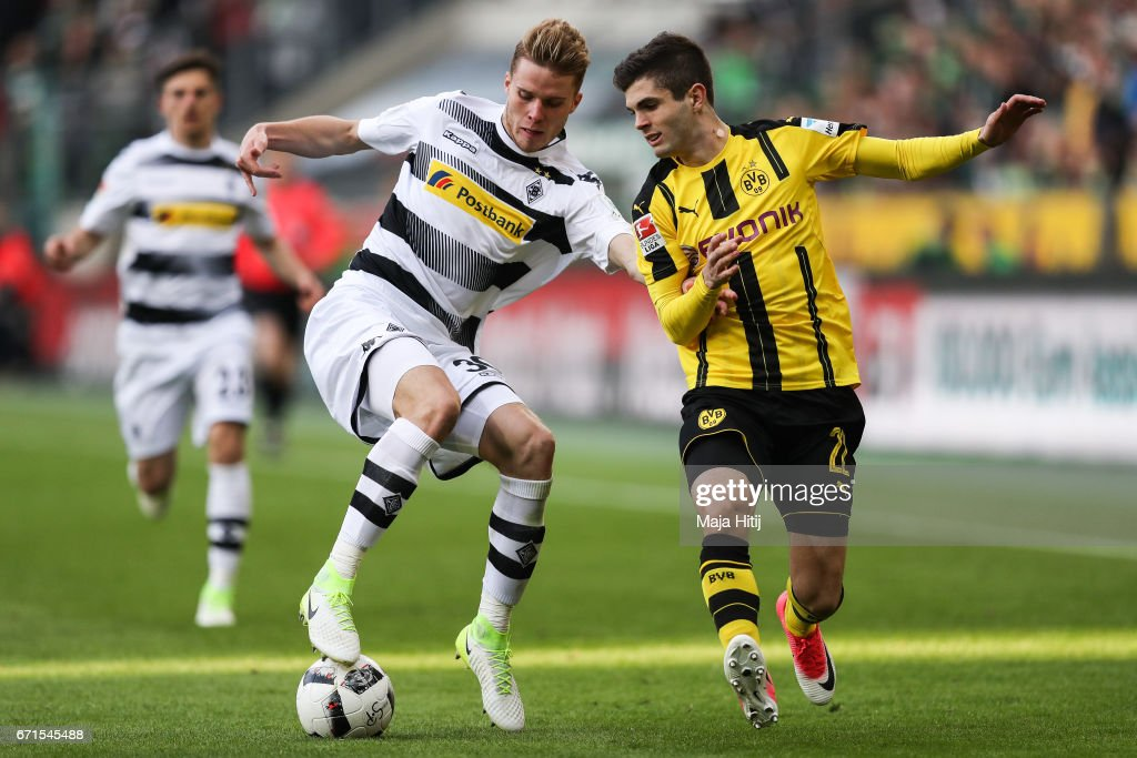 Nico Elvedi of Moenchengladbach and Christian Pulisic of Dortmund battle for the ball during the Bundesliga match between Borussia Moenchengladbach and Borussia Dortmund at Borussia-Park on April 22, 2017 in Moenchengladbach, Germany.