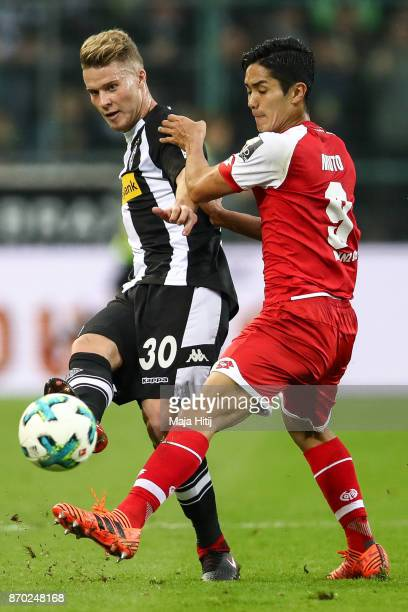Nico Elvedi of Moenchengladbach and Yoshinori Muto of Mainz battle for the ball during the Bundesliga match between Borussia Moenchengladbach and 1...