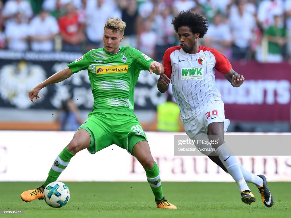 Nico Elvedi of Moenchengladbach (l) fights for the ball with Caiuby of Augsburg during the Bundesliga match between FC Augsburg and Borussia Moenchengladbach at WWK-Arena on August 26, 2017 in Augsburg, Germany.