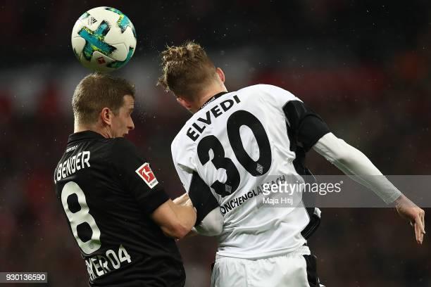 Nico Elvedi of Moenchengladbach fights for the ball with Lars Bender of Bayer Leverkusen during the Bundesliga match between Bayer 04 Leverkusen and...