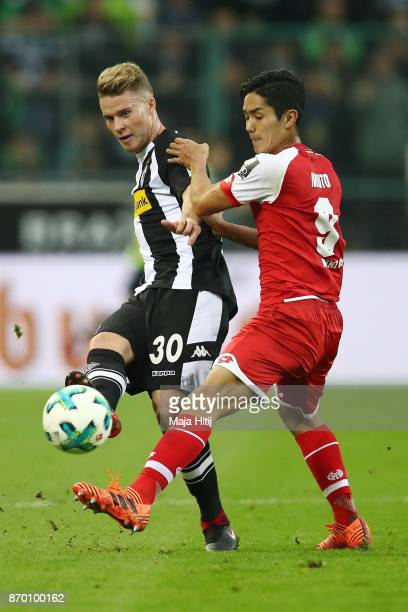 Nico Elvedi of Moenchengladbach fights for the ball with Yoshinori Muto of Mainz during the Bundesliga match between Borussia Moenchengladbach and 1...
