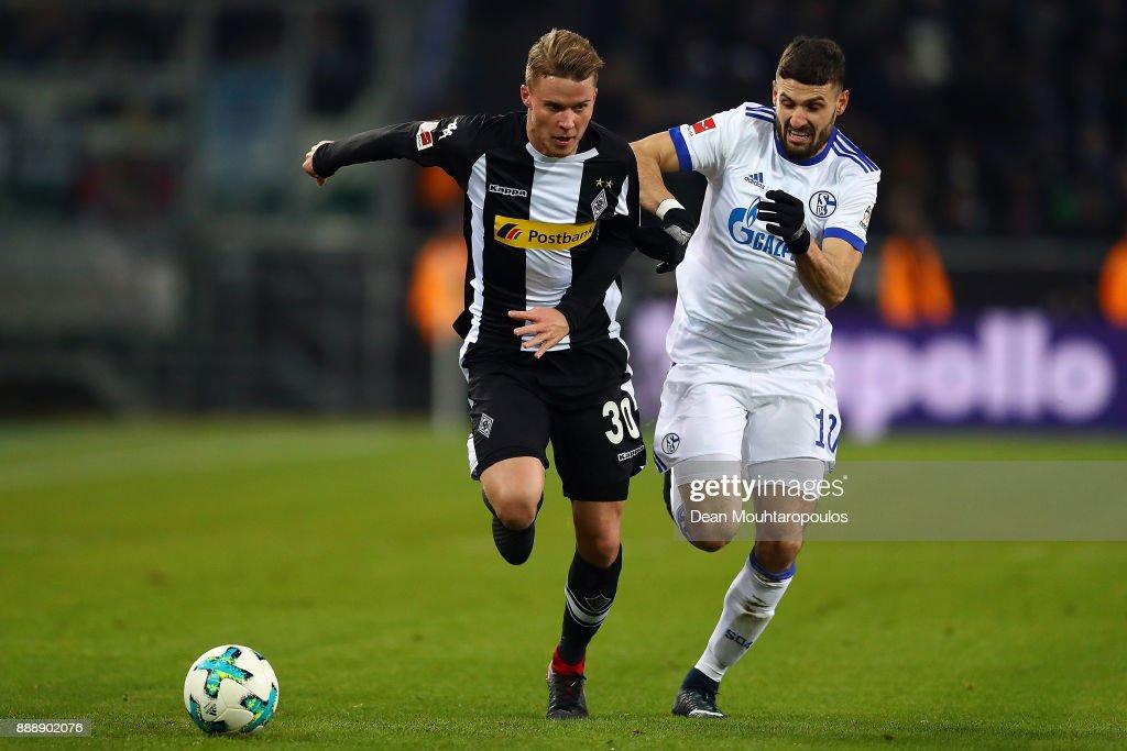 Nico Elvedi of Moenchengladbach (l) runs for the ball with Daniel Caligiuri of Schalke during the Bundesliga match between Borussia Moenchengladbach and FC Schalke 04 at Borussia-Park on December 9, 2017 in Moenchengladbach, Germany.
