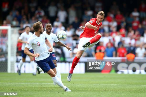 Nico Elvedi of Switzerland shoots while under pressure from Harry Kane of England during the UEFA Nations League Third Place Playoff match between...
