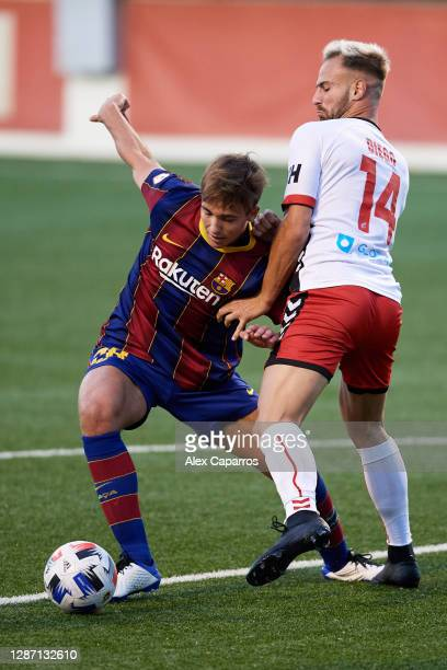 Nico Gonzalez of FC Barcelona B battles for possession with Diego Martinez of CE L'Hospitalet during the Segunda Division B Group IIIA match between...