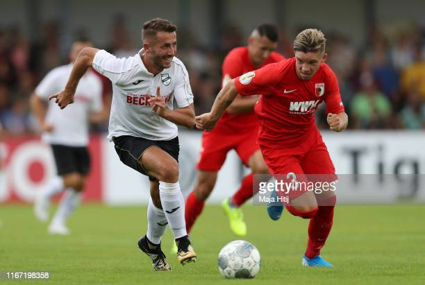 Nico Hecker of SC Verl runs with the ball under pressure from Mads Pedersen of FC Augsburg during the DFB Cup first round match between SC Verl and...