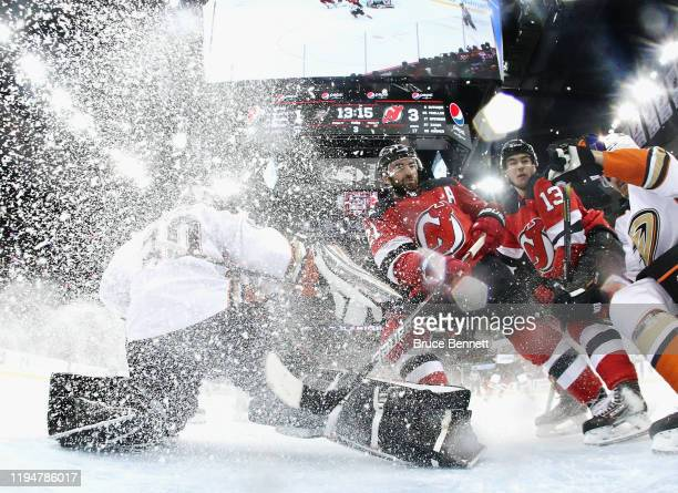 Nico Hischier and Kyle Palmieri of the New Jersey Devils converge on Ryan Miller of the Anaheim Ducks during the third period at the Prudential...