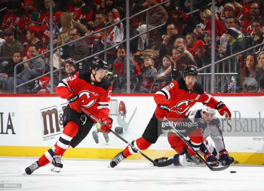 Nico Hischier #13 and Taylor Hall #9 of the New Jersey Devils skate against the Columbus Blue Jackets at the Prudential Center on December 8, 2017 in Newark, New Jersey. The Blue Jackets defeated the Devils 5-3.