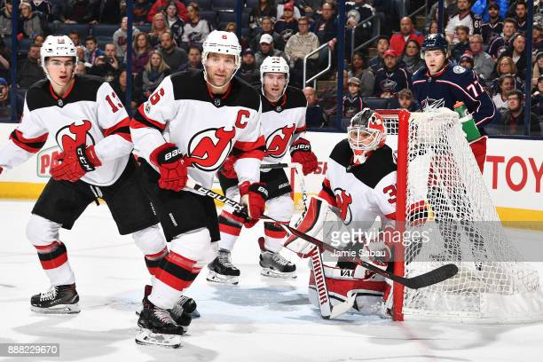 Nico Hischier Andy Greene and Sami Vatanen all of the New Jersey Devils help goaltender Cory Schneider of the New Jersey Devils defend the net...
