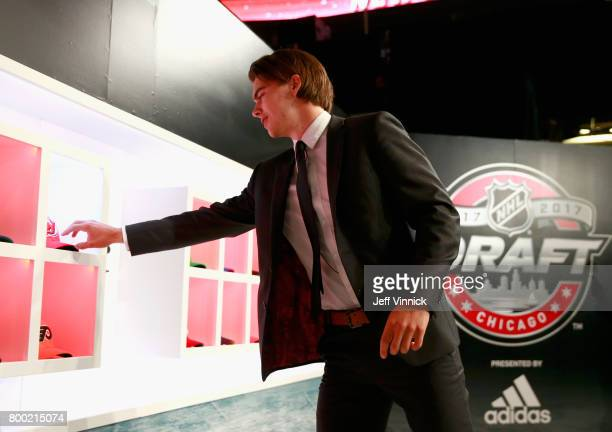 Nico Hischier first overall pick of the New Jersey Devils takes a hat prior to taking the stage during Round One of the 2017 NHL Draft at United...