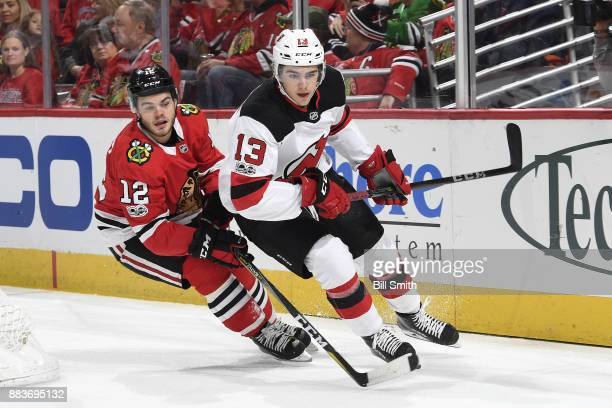 Nico Hischier of the New Jersey Devils and Alex DeBrincat of the Chicago Blackhawks skate in the first period at the United Center on November 12...