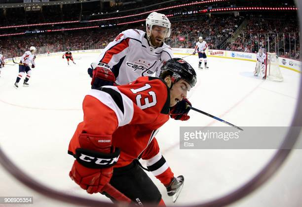 Nico Hischier of the New Jersey Devils and Brooks Orpik of the Washington Capitals fight for the puck on January 18 2018 at Prudential Center in...
