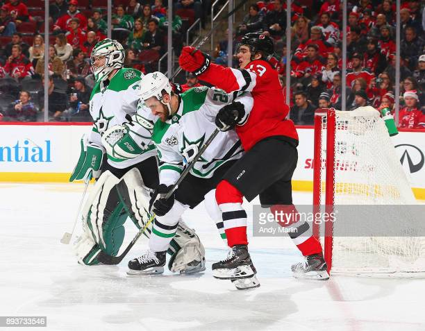 Nico Hischier of the New Jersey Devils and Greg Pateryn of the Dallas Stars battle for position during the game at Prudential Center on December 15...