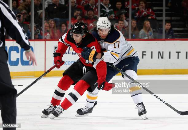 Nico Hischier of the New Jersey Devils and Jordan Nolan of the Buffalo Sabres battle for position during the game at Prudential Center on December 29...