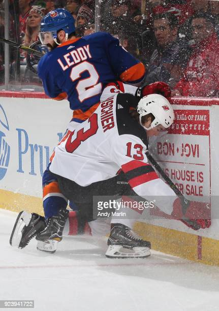 Nico Hischier of the New Jersey Devils and Nick Leddy of the New York Islanders come together at the boards during the game at Prudential Center on...