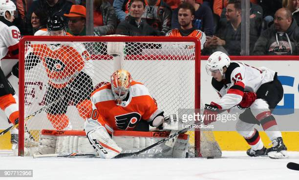 Nico Hischier of the New Jersey Devils attempts a wraparound scoring chance against Michal Neuvirth of the Philadelphia Flyers on January 20 2018 at...