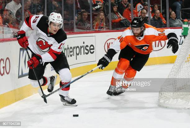 Nico Hischier of the New Jersey Devils attempts to control the puck behind the net while being pursued by Sean Couturier of the Philadelphia Flyers...
