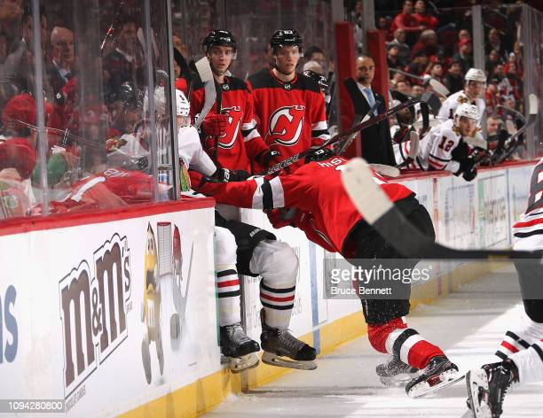 Nico Hischier of the New Jersey Devils checks Connor Murphy of the Chicago Blackhawks into the Devils bench during the third period at the Prudential...