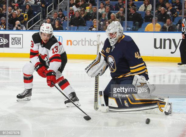 Nico Hischier of the New Jersey Devils deflects the puck as Robin Lehner of the Buffalo Sabres defends during the second period of an NHL game on...