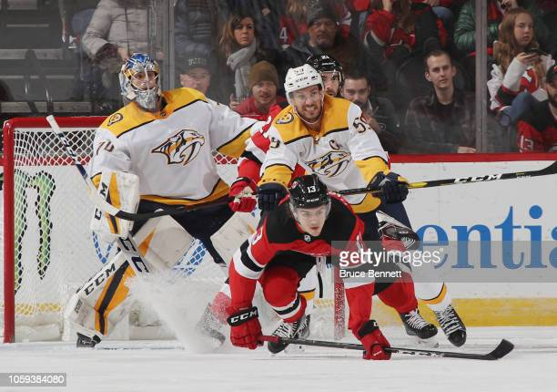Nico Hischier of the New Jersey Devils is hit by Roman Josi of the Nashville Predators during the first period at the Prudential Center on October 25...