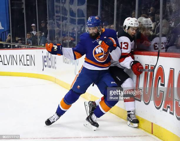 Nico Hischier of the New Jersey Devils is hit into the boards by Nick Leddy of the New York Islanders during the first period at the Barclays Center...