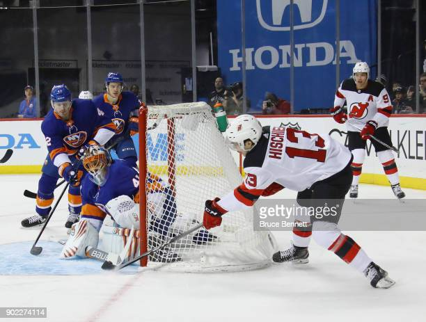 Nico Hischier of the New Jersey Devils is stopped by Jaroslav Halak of the New York Islanders during the first period at the Barclays Center on...