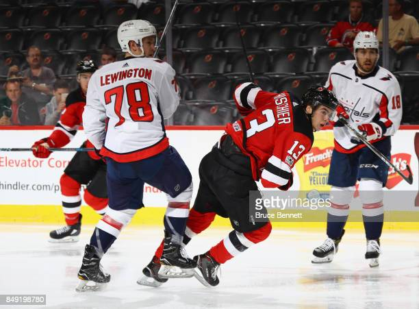 Nico Hischier of the New Jersey Devils is tripped up by Tyler Lewington of the Washington Capitals during a preseason game at the Prudential Center...
