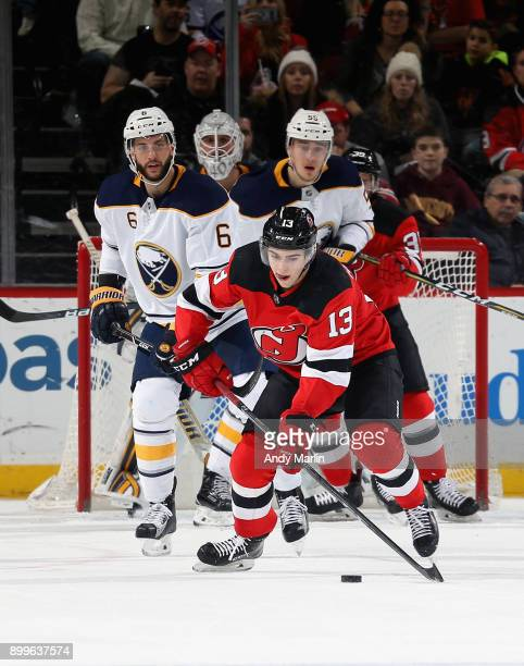 Nico Hischier of the New Jersey Devils plays the puck away from Marco Scandella of the Buffalo Sabres during the game at Prudential Center on...