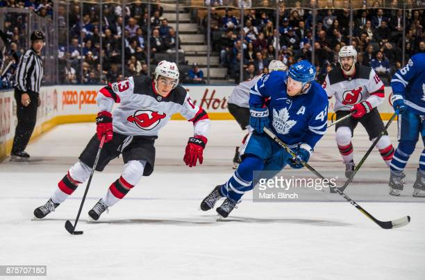 Nico Hischier of the New Jersey Devils skates against Morgan Rielly of the Toronto Maple Leafs during the second period at the Air Canada Centre on...