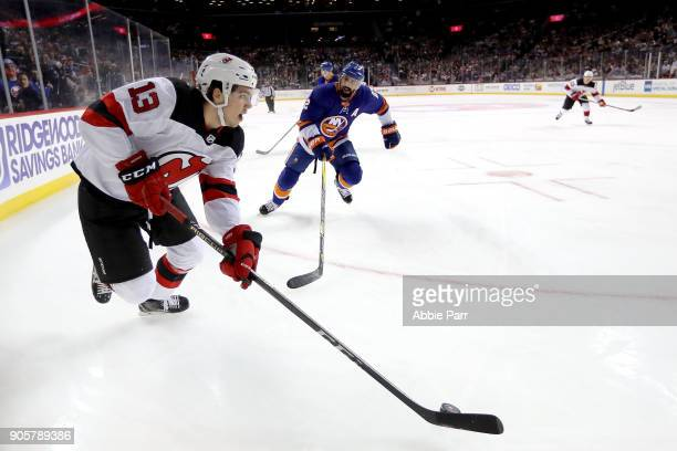 Nico Hischier of the New Jersey Devils skates with the puck against Nick Leddy of the New York Islanders in the first period during their game at...