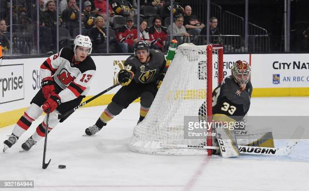 Nico Hischier of the New Jersey Devils skates with the puck against Nate Schmidt of the Vegas Golden Knights as Maxime Lagace tends net in the third...