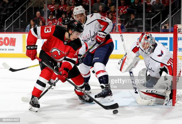 Nico Hischier of the New Jersey Devils takes a shot as John Carlson and Braden Holtby of the Washington Capitals defends in the second period on...