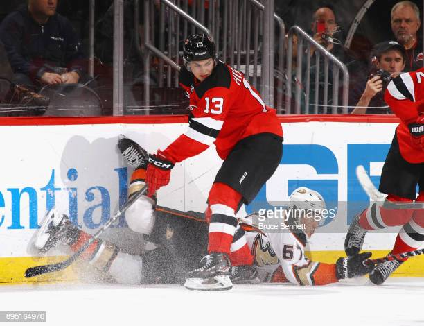 Nico Hischier of the New Jersey Devils trips up Rickard Rakell of the Anaheim Ducks during the third period at the Prudential Center on December 18...